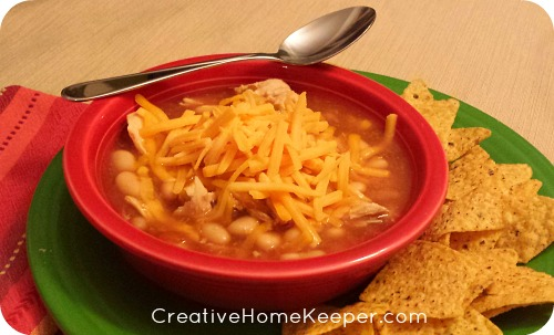 This warm and comforting white bean chicken chili is super easy to make using only 4 ingredients, and is so delicious! Cooks all day in the slow cooker for those busy days. This soup feeds a crowd and is SO YUMMY!!!! | CreativeHomeKeeper.com